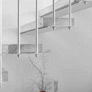 Foto di un piccolo soggiorno moderno aperto con pareti grigie, pavimento in travertino, TV a parete e pavimento rosa