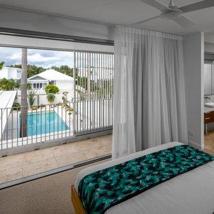 Immagine di un piccolo soggiorno minimalista aperto con pareti grigie, pavimento in travertino, TV a parete e pavimento rosa