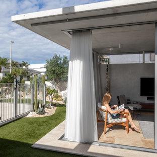 Kleines, Offenes Retro Wohnzimmer mit grauer Wandfarbe, Travertin, Wand-TV und rosa Boden in Gold Coast - Tweed