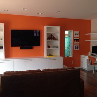 Inspiration for a mid-sized modern open concept medium tone wood floor family room remodel in Los Angeles with orange walls, no fireplace and a wall-mounted tv