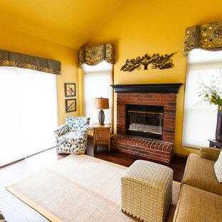 カンザスシティの中サイズのトラディショナルスタイルのおしゃれなファミリールーム (ベージュの壁、無垢フローリング、標準型暖炉、レンガの暖炉まわり、茶色い床) の写真