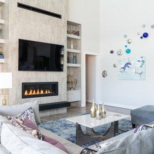 オースティンの大きいコンテンポラリースタイルのおしゃれなファミリールーム (無垢フローリング、横長型暖炉、タイルの暖炉まわり、壁掛け型テレビ、グレーの床、グレーの壁) の写真