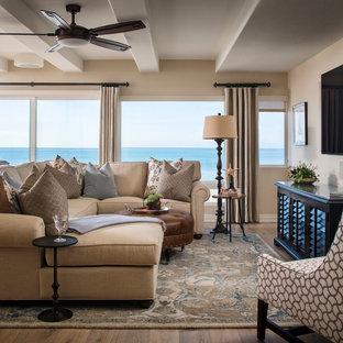 オレンジカウンティの中サイズのビーチスタイルのおしゃれなファミリールーム (茶色い壁、濃色無垢フローリング、壁掛け型テレビ、茶色い床) の写真