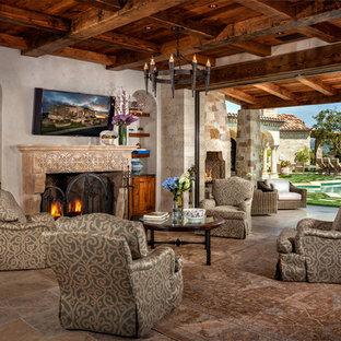 Offenes Mediterranes Wohnzimmer mit beiger Wandfarbe, Kamin, Wand-TV und beigem Boden in Orange County