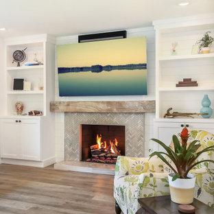 Exemple d'une grand salle de séjour tendance ouverte avec un mur blanc, un sol en bois brun, une cheminée standard, un manteau de cheminée en carrelage, un téléviseur fixé au mur et un sol marron.