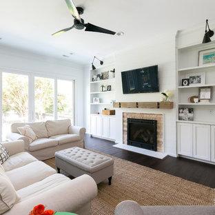 Imagen de sala de estar abierta, campestre, grande, con paredes blancas, chimenea tradicional, marco de chimenea de ladrillo y televisor colgado en la pared
