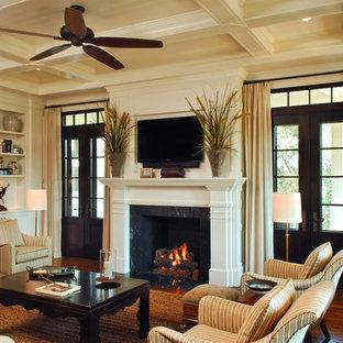 チャールストンのトラディショナルスタイルのおしゃれなファミリールーム (ベージュの壁、濃色無垢フローリング、標準型暖炉、壁掛け型テレビ、茶色い床) の写真