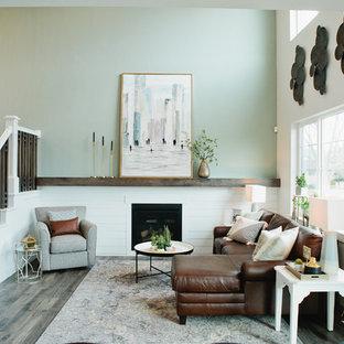 Esempio di un piccolo soggiorno stile americano stile loft con pareti grigie, pavimento in laminato, camino classico, TV a parete e pavimento grigio