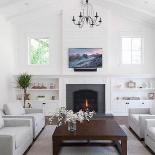 バンクーバーのビーチスタイルのおしゃれなファミリールーム (白い壁、濃色無垢フローリング、標準型暖炉、壁掛け型テレビ、茶色い床) の写真