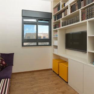 Cette image montre une petite salle de séjour mansardée ou avec mezzanine bohème avec salle de jeu, un sol en contreplaqué, aucune cheminée et un téléviseur encastré.