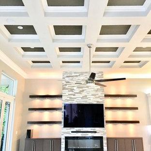 Foto di un grande soggiorno minimalista aperto con pareti grigie, pavimento in marmo, camino sospeso, cornice del camino in pietra ricostruita, TV a parete, pavimento beige e soffitto a cassettoni