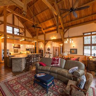他の地域の広いラスティックスタイルのおしゃれなオープンリビング (ベージュの壁、両方向型暖炉、石材の暖炉まわり、テレビなし、濃色無垢フローリング、マルチカラーの床) の写真