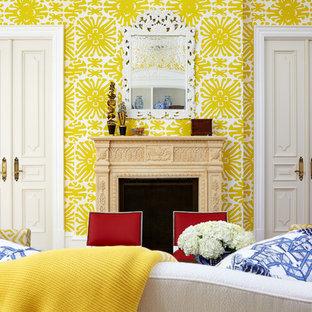 Imagen de sala de estar cerrada, tradicional renovada, de tamaño medio, sin televisor, con paredes amarillas, suelo de madera clara, chimenea tradicional y marco de chimenea de piedra