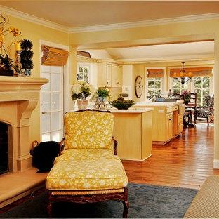 Klassisches Wohnzimmer mit beiger Wandfarbe, braunem Holzboden, Kamin und Kaminumrandung aus Stein in Seattle