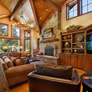 Exemple d'une très grande salle de séjour sud-ouest américain ouverte avec un sol en bois brun, une cheminée standard, un manteau de cheminée en pierre, un téléviseur encastré et un mur jaune.