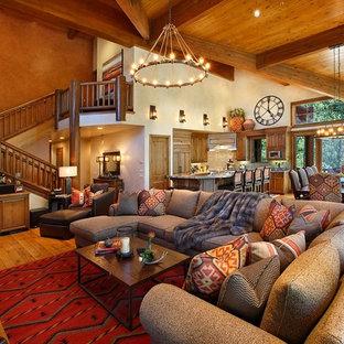 Aménagement d'une très grande salle de séjour sud-ouest américain ouverte avec un mur orange, un sol en bois brun, une cheminée standard, un manteau de cheminée en pierre et un téléviseur encastré.