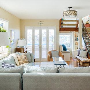 Imagen de sala de estar cerrada, costera, de tamaño medio, sin chimenea, con paredes beige, suelo de madera clara y suelo marrón