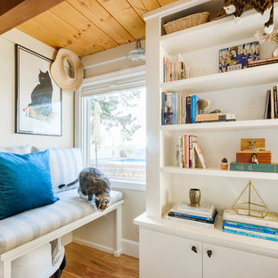 Inspiration for a mid-sized coastal enclosed light wood floor and brown floor family room library remodel in San Diego with beige walls and no fireplace