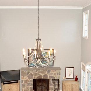 Großes, Offenes Klassisches Wohnzimmer mit grauer Wandfarbe, braunem Holzboden, Kamin, Kaminumrandung aus Stein und Eck-TV in New York