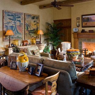 Foto di un grande soggiorno stile rurale aperto con pareti beige, pavimento in legno massello medio, camino classico, cornice del camino piastrellata e TV nascosta