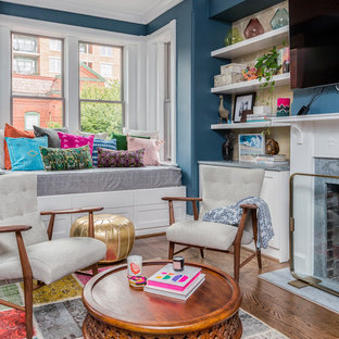 Example of an eclectic dark wood floor family room design in DC Metro with blue walls, a standard fireplace and a wall-mounted tv