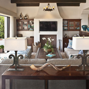 This is an example of a mid-sized mediterranean open concept family room in Los Angeles with beige walls, dark hardwood floors, a wall-mounted tv, no fireplace and brown floor.