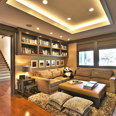 Example of a trendy medium tone wood floor family room design in Los Angeles with beige walls