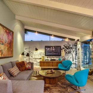 Diseño de sala de estar vintage con paredes verdes, chimenea tradicional, marco de chimenea de piedra y televisor colgado en la pared