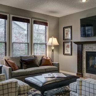 Ejemplo de sala de estar abierta, tradicional renovada, pequeña, con paredes grises, suelo de madera clara, chimenea tradicional, televisor colgado en la pared y marco de chimenea de piedra