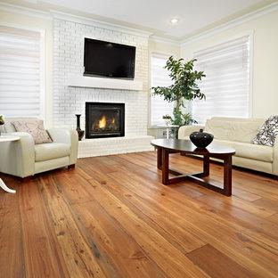 エドモントンのコンテンポラリースタイルのおしゃれなファミリールーム (ベージュの壁、無垢フローリング、標準型暖炉、レンガの暖炉まわり、壁掛け型テレビ、茶色い床) の写真