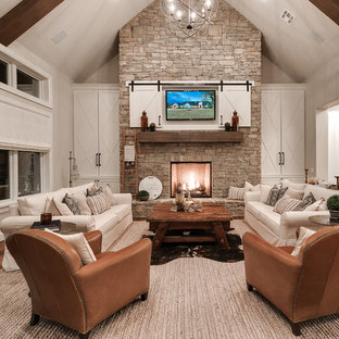 This is an example of a rural open plan family and games room in Oklahoma City with beige walls, light hardwood flooring, a standard fireplace, a stone fireplace surround, a wall mounted tv and beige floors.