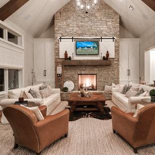 Foto de sala de estar abierta, de estilo de casa de campo, con paredes beige, suelo de madera clara, chimenea tradicional, marco de chimenea de piedra, televisor colgado en la pared y suelo beige