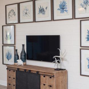 ジャクソンビルの広いビーチスタイルのおしゃれなオープンリビング (白い壁、セラミックタイルの床、壁掛け型テレビ、ベージュの床) の写真