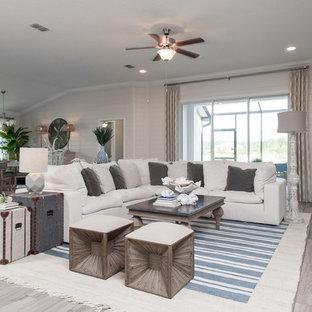 ジャクソンビルの大きいビーチスタイルのおしゃれなファミリールーム (白い壁、セラミックタイルの床、壁掛け型テレビ、ベージュの床) の写真