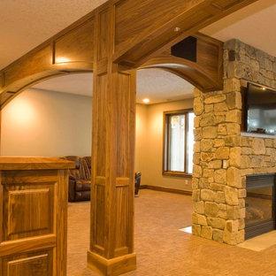 カルガリーのトラディショナルスタイルのおしゃれなファミリールーム (ベージュの壁、カーペット敷き、両方向型暖炉、石材の暖炉まわり、壁掛け型テレビ) の写真