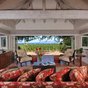 Esempio di un soggiorno tropicale di medie dimensioni e aperto con pareti bianche, pavimento in terracotta, nessun camino, nessuna TV e pavimento rosso