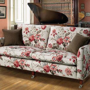 Diseño de sala de estar con biblioteca abierta, retro, de tamaño medio, sin chimenea y televisor, con paredes rosas, suelo de madera oscura, marco de chimenea de ladrillo y suelo marrón