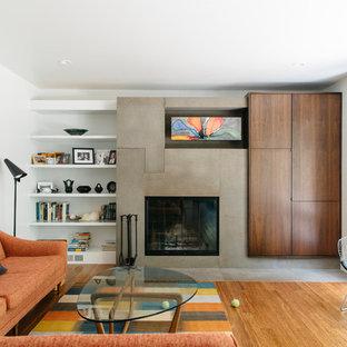 Mittelgroßes, Abgetrenntes Mid-Century Wohnzimmer mit weißer Wandfarbe, Bambusparkett, Kamin, Kaminsims aus Beton und verstecktem TV in Omaha