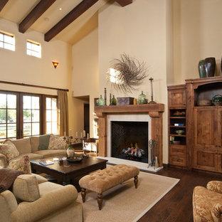 Exemple d'une grande salle de séjour méditerranéenne ouverte avec un mur beige, un sol en bois foncé, une cheminée standard, un manteau de cheminée en bois, un sol marron et un téléviseur dissimulé.