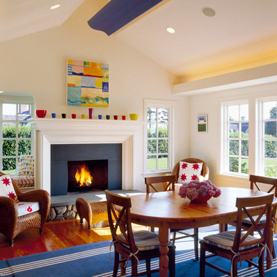 Inspiration for an eclectic medium tone wood floor family room remodel in Boston with beige walls, a standard fireplace and a stone fireplace