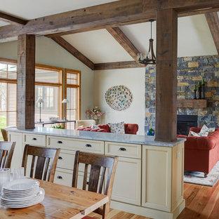 Idée de décoration pour une salle de séjour craftsman de taille moyenne et ouverte avec un mur beige, un sol en bois clair, une cheminée standard, un manteau de cheminée en pierre et aucun téléviseur.