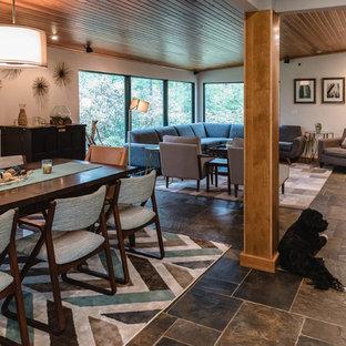 デトロイトの中くらいのミッドセンチュリースタイルのおしゃれなオープンリビング (白い壁、スレートの床、標準型暖炉、タイルの暖炉まわり、壁掛け型テレビ、グレーの床) の写真