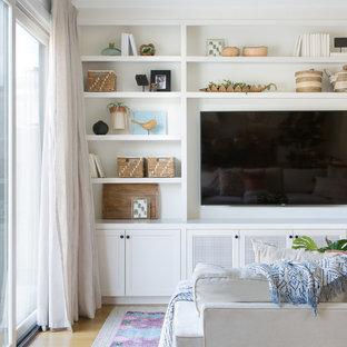 Imagen de sala de estar abierta, de estilo de casa de campo, de tamaño medio, con paredes blancas, suelo de madera clara, pared multimedia y suelo beige