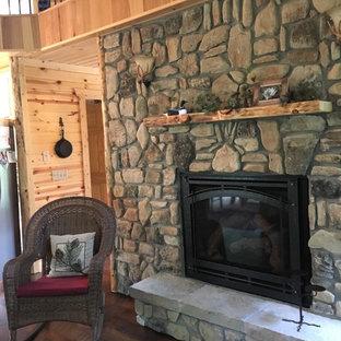 他の地域のラスティックスタイルのおしゃれなオープンリビング (茶色い壁、濃色無垢フローリング、標準型暖炉、石材の暖炉まわり、テレビなし、茶色い床) の写真