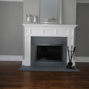 ニューヨークの中サイズのトラディショナルスタイルのおしゃれなファミリールーム (標準型暖炉、グレーの壁、濃色無垢フローリング、タイルの暖炉まわり) の写真