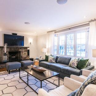 モントリオールの中くらいのモダンスタイルのおしゃれな独立型ファミリールーム (青い壁、無垢フローリング、標準型暖炉、石材の暖炉まわり、壁掛け型テレビ、茶色い床) の写真