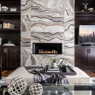Foto di un soggiorno tradizionale di medie dimensioni e chiuso con pareti grigie, parquet scuro, camino lineare Ribbon, parete attrezzata, libreria e cornice del camino piastrellata