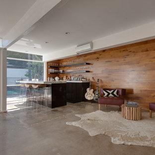 オレンジカウンティのコンテンポラリースタイルのおしゃれなファミリールーム (コンクリートの床、茶色い壁、茶色い床) の写真