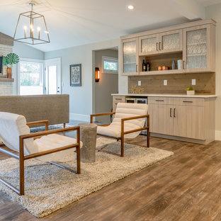 デンバーの大きいモダンスタイルのおしゃれなファミリールーム (グレーの壁、ラミネートの床、標準型暖炉、レンガの暖炉まわり、壁掛け型テレビ、グレーの床) の写真