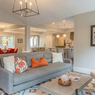 デンバーの大きいコンテンポラリースタイルのおしゃれなファミリールーム (グレーの壁、ラミネートの床、標準型暖炉、レンガの暖炉まわり、壁掛け型テレビ、グレーの床) の写真